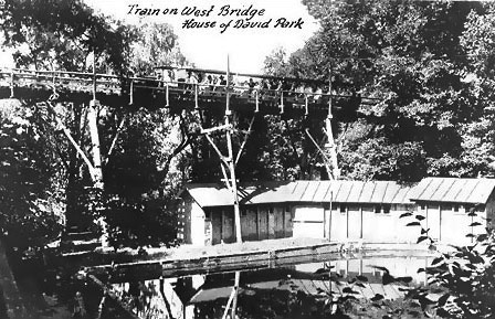 With all the colonists had to do to open the Eden Springs Park in 1908 they found time to construct a high railroad trestle over the creek valley in the center of the park.  This trestle was at the west end of the valley and is shown in the earliest pictures of the park.  It is not clear today how this trestle was used before the east trestle was built a short time later.  Trains may have run forward over the trestle in one direction and in reverse over it in the other direction.  Another possibility is that the train looped on each side of the trestle.  The west trestle ran just to the west of a pond made by impounding the creek that ran through the Eden Springs Valley.  In the foreground are buildings that were used as changing rooms for swimming.  The train in this image is heading south from the north depot to the south depot.  This was most common direction of travel during the history of the railroad.  In later years park visitors could see trains pass on this trestle behind the beer garden stage while watching shows at the park.  The Eden Springs creek ran from the pond, over a spillway, under this trestle and out of the park.