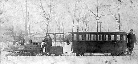 To honor founders Mary and Benjamin, colony members constructed an enclosed passenger car for their privacy and protection from the elements when riding on the trains.  This car was rarely used and only in the early years.  Because of the narrow gauge tracks and the heavy superstructure of this car it was unstable and could only be run on the curves at slow speed.  An interesting feature of this image is a rare glimpse just above the front of the locomotive of the park dance pavilion that would later become a roundhouse.