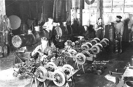 The first four 4-4-0 miniature locomotives built at the park are shown here disassembled in a colony machine shop.  This photograph does not represent the original construction according to Earl Boyersmith (second from the right in the picture), who lived close by the Colony (passed away July 25, 2006).  Every winter the locomotives and cars had to be overhauled because of the heavy use they received during the tourist season.  Each drive and guide wheel on the locomotives as well as the wheels on the passenger cars had to be machined on lathes to remove flat spots worn during the summer rail service.