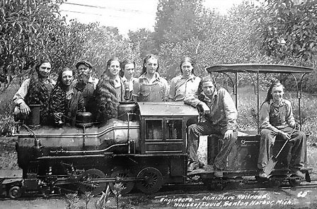 The 4-6-0 ''Ten Wheelers'' produced at the park after the little 4-4-0 engines and were of a similar design.  This detailed picture of one of these engines includes a group of the boy engineers used in those days to run the trains.  A second crew member on each train was the conductor who had overall responsibility for the train and communicated to the engineer via a bell placed on the front of the first car.  This bell was connected to the back of the end car by means of a rope which ran under the canopy of all the passenger cars in the train.  The conductor used this bell from his base of operations at the back of the train to signal to the engineer at the front when to leave the station.  The conductor's job included punching tickets which passengers purchased at the depot and making sure passengers were seated and bystanders out of the way when the train departed the station.  The conductor was also responsible for signaling the roundhouse via an electric bell system when additional trains needed to be put into service based on the crowds waiting at the depots.
